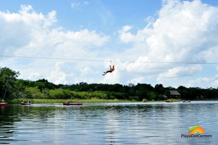Person zip lining across lake