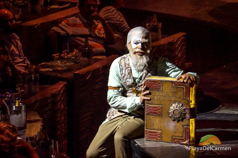 An actor sitting on stage with a book at Cirque Du Soleil theater in the Riviera Maya