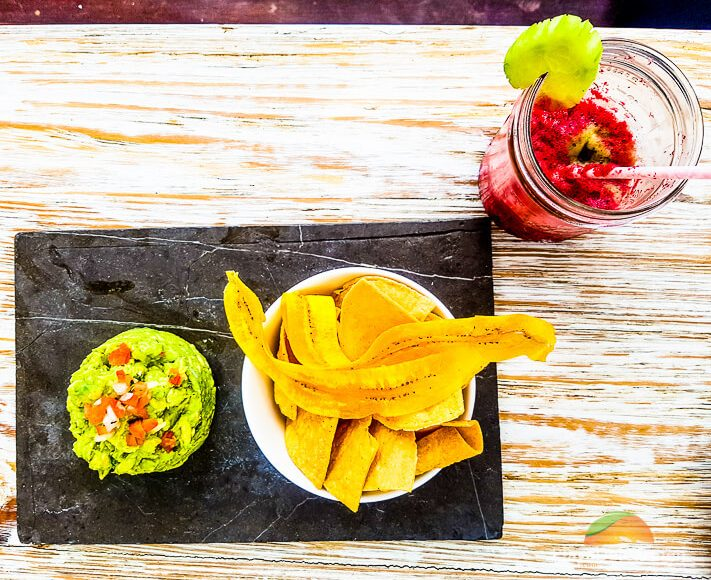 fresh-made guacamole served with tortilla chips and fried plantains at inti beach club