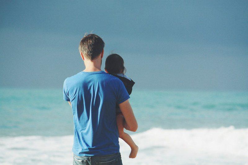 Man holds child at Playa del Carmen beach