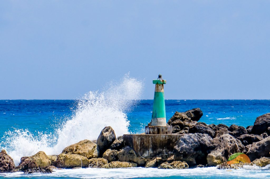 Waves crashing against the min-light tower in Puerto Aventuras